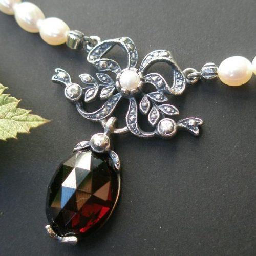 Perlenkette mit Schleife in der Mitte eine Süßwasserperle und Granat Tropfen