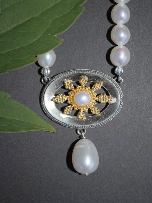 Schöne Perlenkette mit einem oval-förmigen Mittelteil aus SIlber der von einem vergoldeten Stern verziert wird.