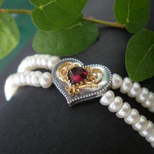 Perlenarmband mit Herzmotiv und goldenene Details in der Mitte geziert von einem Granat
