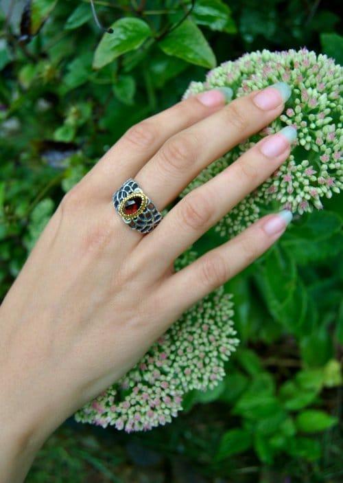 Ring aus Silber mit Gitteroptik und Granat gefasst auf Hand getragen