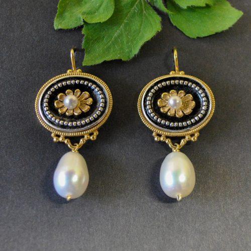 Schwarze Ohrringe mit vergoldeten Details und Perle