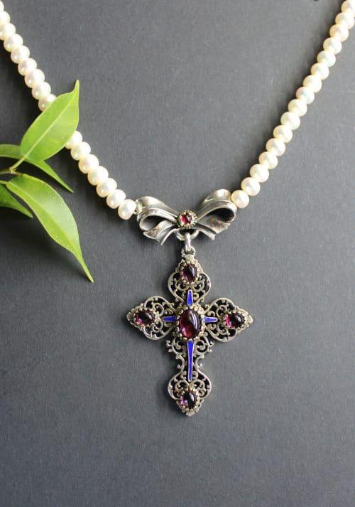 Trachtenschmuck mit Perlen: Perlenkette Susi, sehr detailreiches Silbermittelteil in Kreuzform gefasst mit mehreren Schmucksteinen in Granat und blauem Emaille