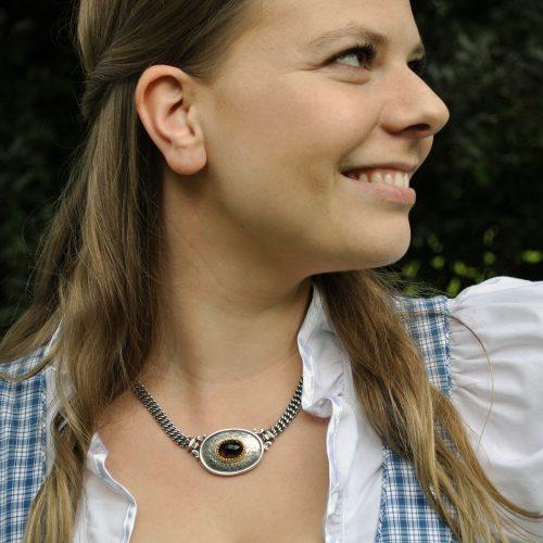 Frau im Dirndl trägt Silberkette mit Granat