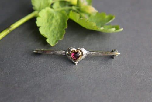 Längliche Brosche in Silber und mit Granat in Herzform gefasst