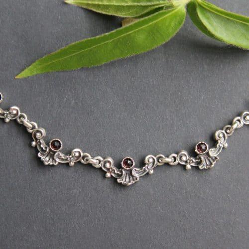 Trachtenkette für Damen: Silberne, zierliche Halskette zum Dirndl mit kleinen Granat Schmucksteinen
