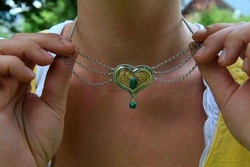 Frau trägt Trachtenkette mit Herzmotiv in Händen