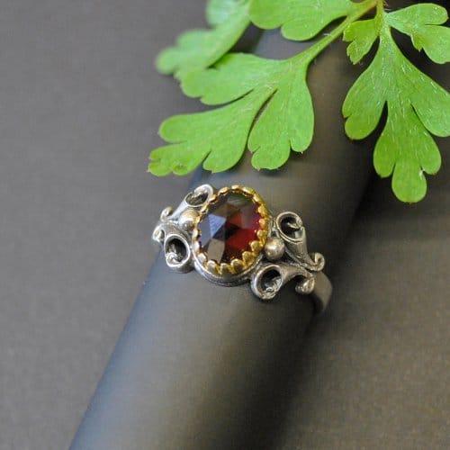 Trachtiger Ring aus Silber mit Granatstein in der MItte gefasst
