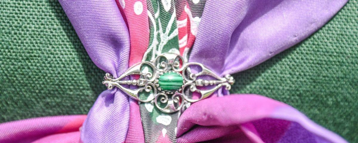 Trachtenbrosche Silber mit Smaragd an Dirndltuch angeheftet