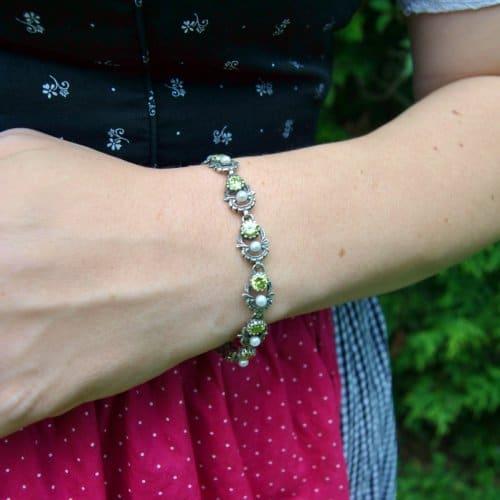 Dirndl trägt Trachtenarmband Jutta mit Perlen und grünem Zirkonia