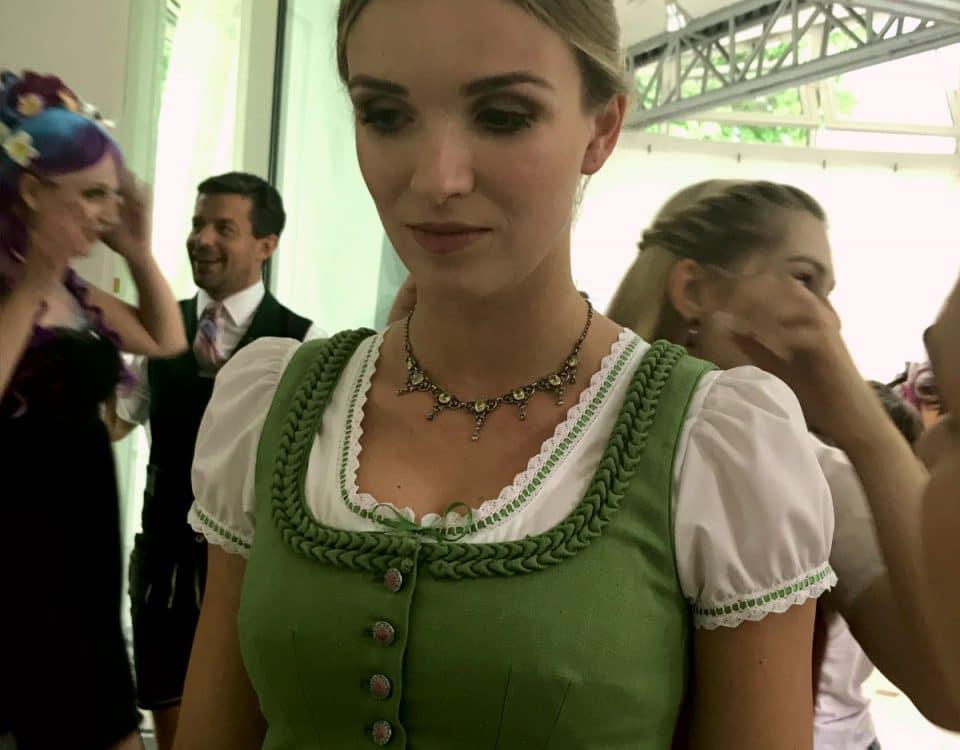 Frau im Dirndl mit grünem Oberteil und Silberkette mit grünen Details