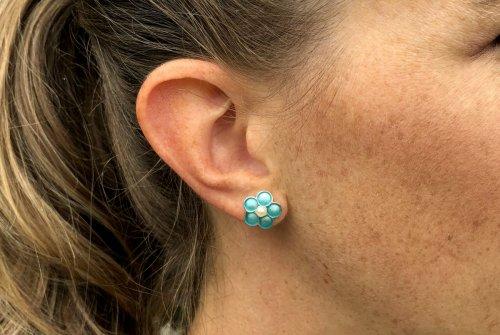 Blumige Ohrringe aus blauem Email getragen