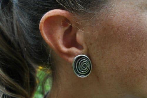 Ohrringe aus Silber in Schneckenoptik getragen