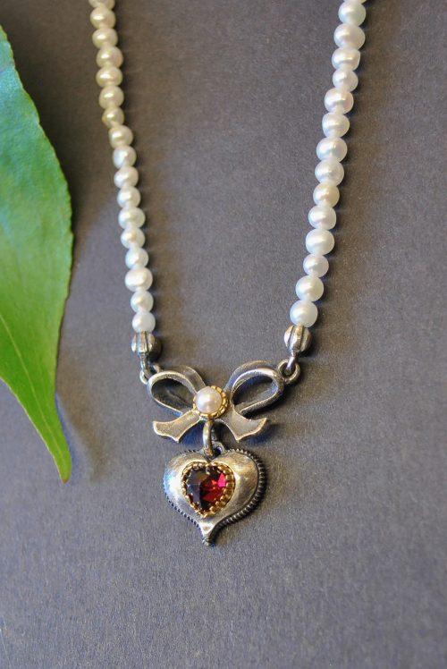 Perlenkette von Seite mit Schleife und Herz