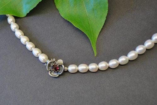 Silberne Schließe Lilli mit Granat an Perlenhalskette angebracht