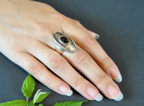 Schöner Trachtenring aus Silber und einem Granat gefasst, getragen an einer Hand