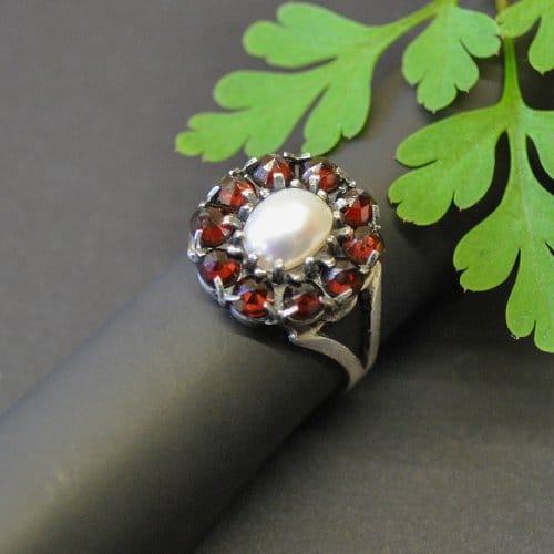 Granatschmuck Ring: Blumenförmiger Trachtenring gefasst mit Granat und einer Perle