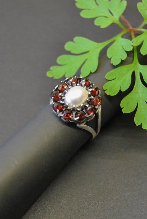 Blumenförmiger Trachtenring gefasst mit Granat und einer Perle