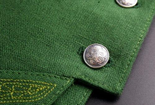 Silberknopf mit Blumenmotiv in grünem Männergilet