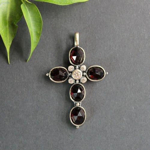 Anhänger in Silber als Kreuz mit facettiertem Granat und Zirkonia