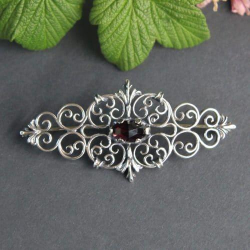 Trachtenbrosche in Silber mit Granat und Schnörkelmuster