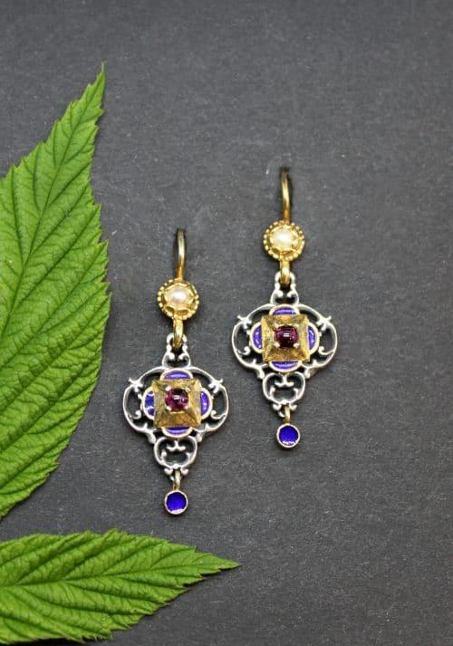 Traditionelle Trachtenschmuck Ohrringe in Silber und vergoldeten und emaillierten Details in Blau. Der Ohrschmuck ist mit Granat gefasst
