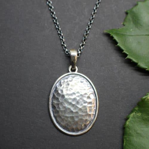 Schlichter, ovaler Trachtenschmuck Anhänger mit gehämmerter Platte in Silber an einer Erbskette in Altsilber