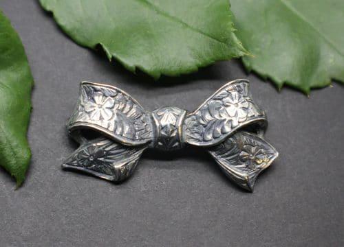 Trachtenschmuck Brosche in Silber, Form Schleife mit Blumenmuster