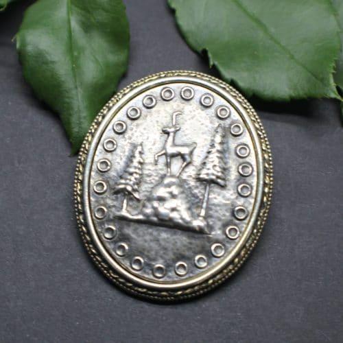 Silberne Trachtenschmuck Brosche oval mit Motiv Gamserl und Bäume, der Rand der Brosche ist vergoldet