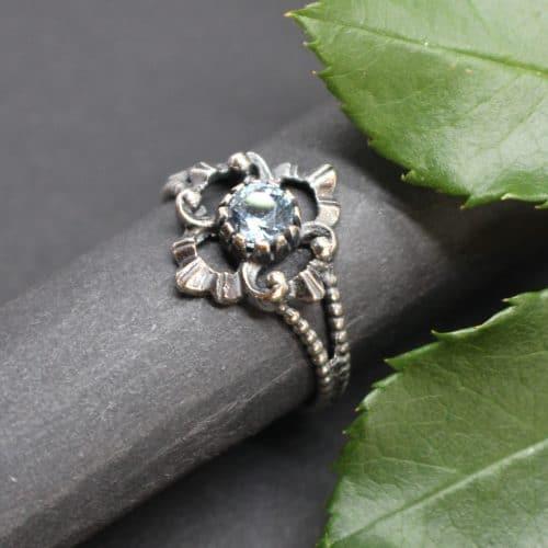 Seitliche Ansicht des Trachtenschmuck Rings in Silber. Der Ring ist mit synthetischem Spinell, einem hellblauen Edelstein gefasst. In den gängigsten Ringgrößen erhältlich.